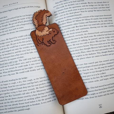 Hand-tooled brown leather skunk bookmark.