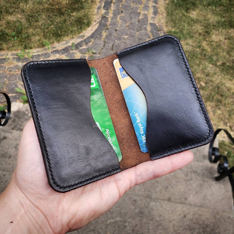 Black leather wallet, open to show two card slots with cards in them.