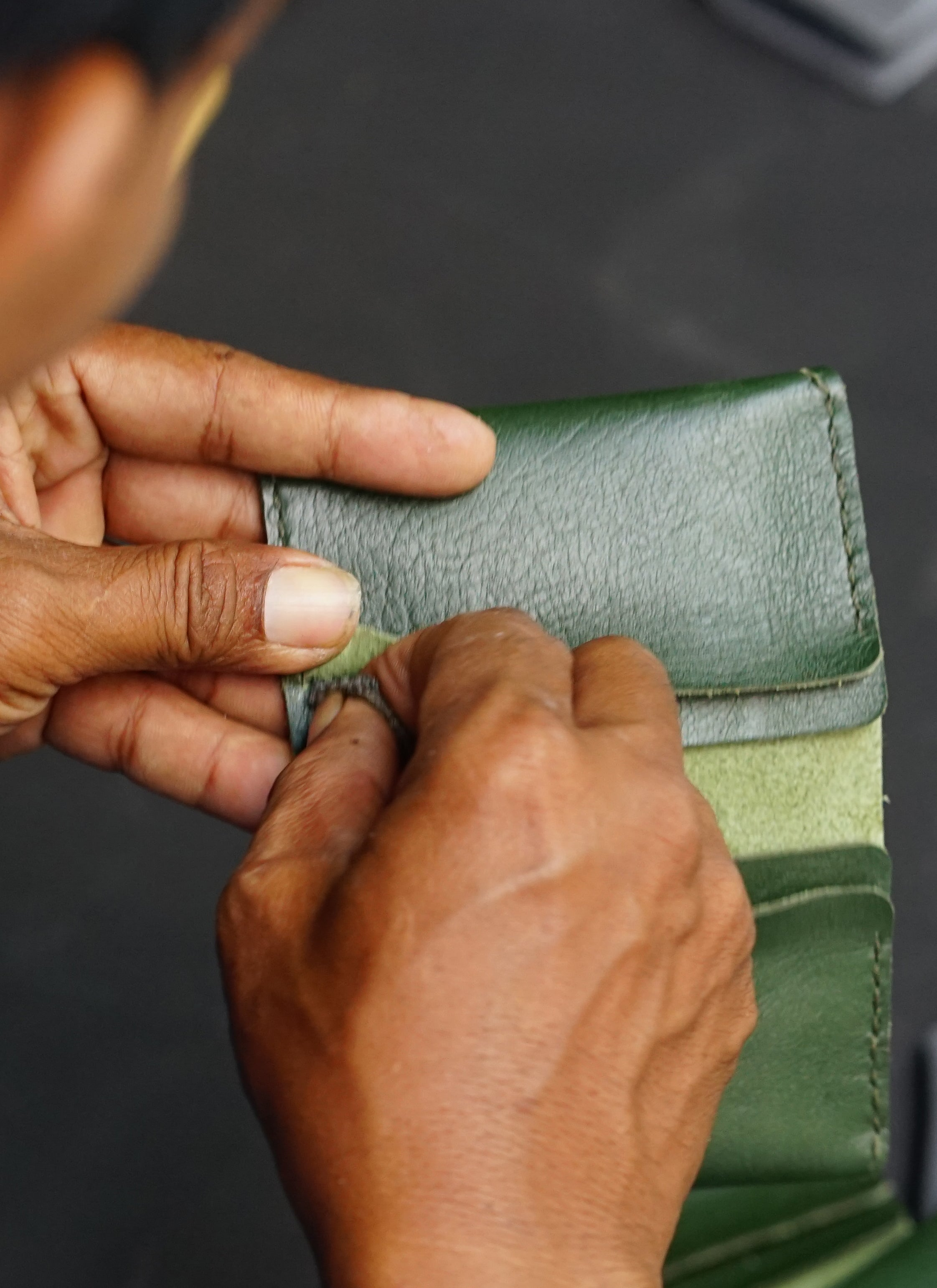 Artisan hand sewing the pocket seams of an olive card case.