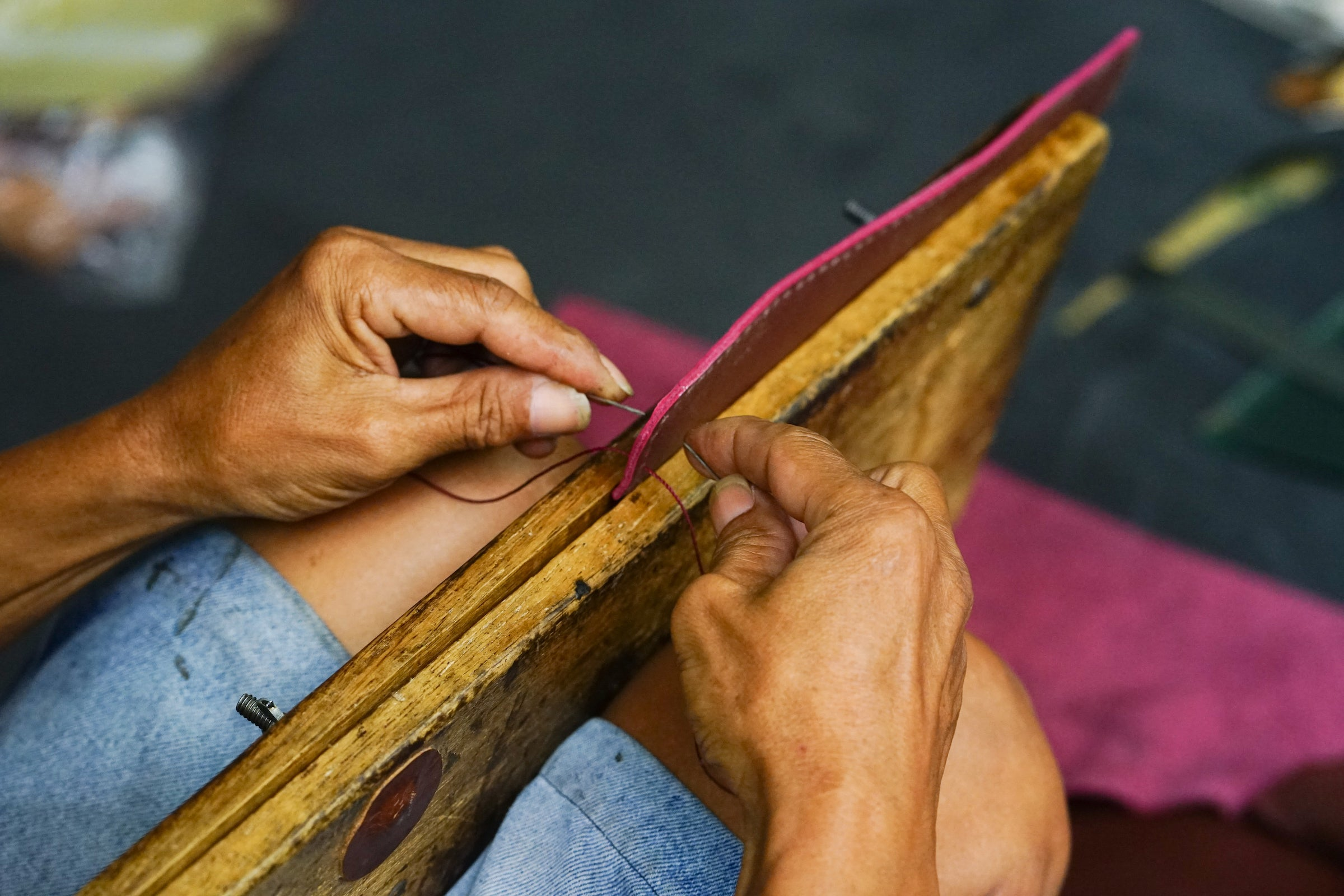 Artisan hand sewing two pieces of burgundy leather held together with a flat wooden clamp held in place with his knees.