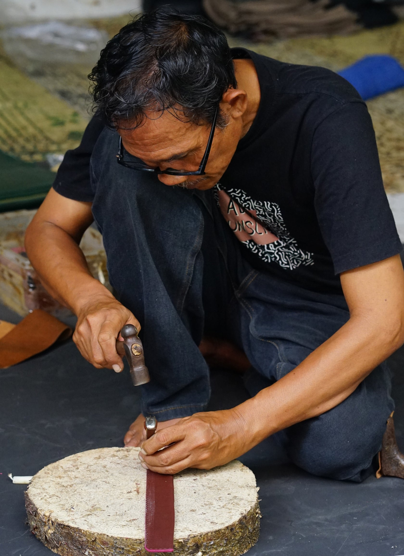 An artisan punches a hole in a leather strip with a hammer and tool.