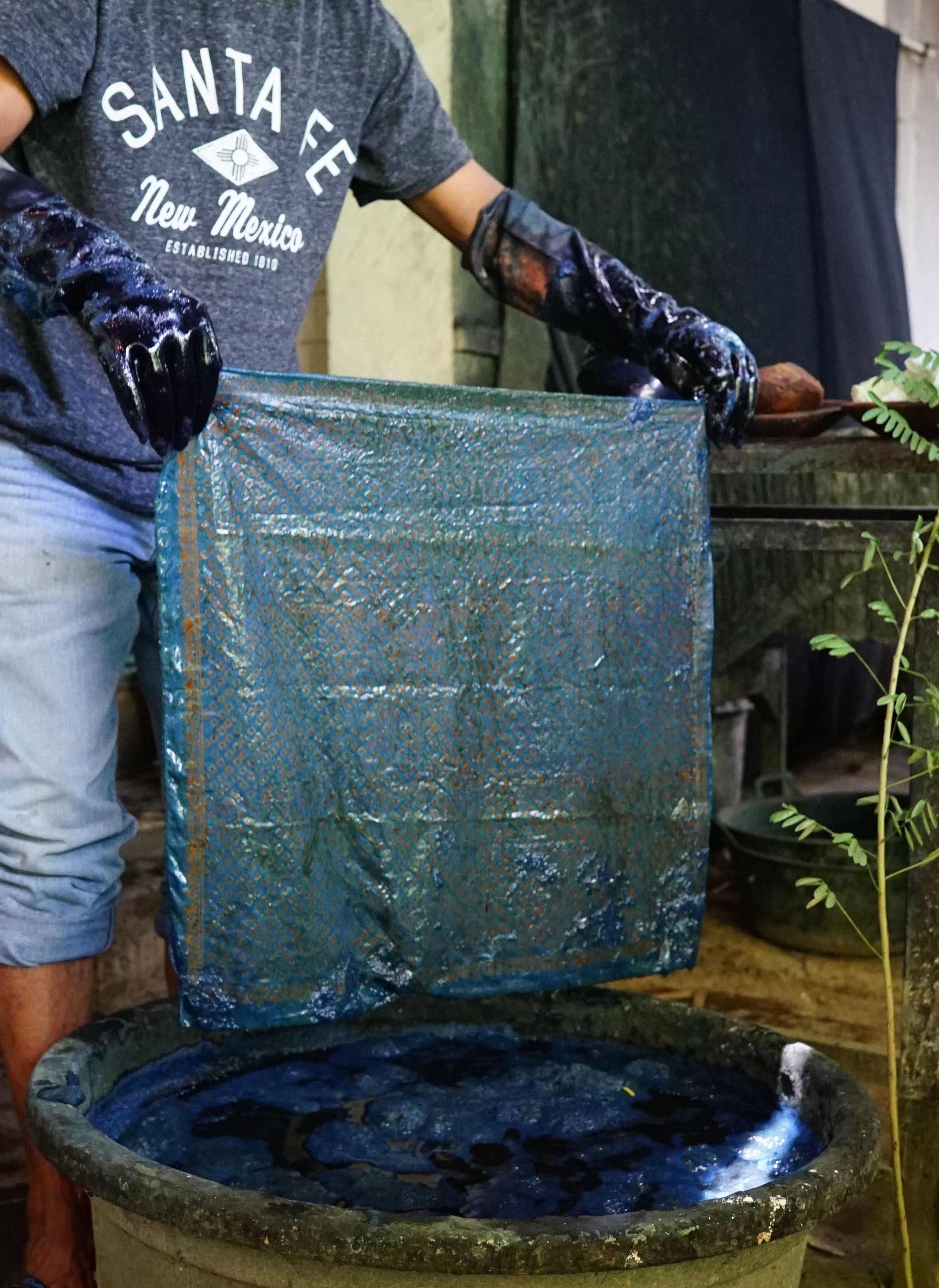 Artisan lifting a batik bandana out of a dying barrel with gloved hands.
