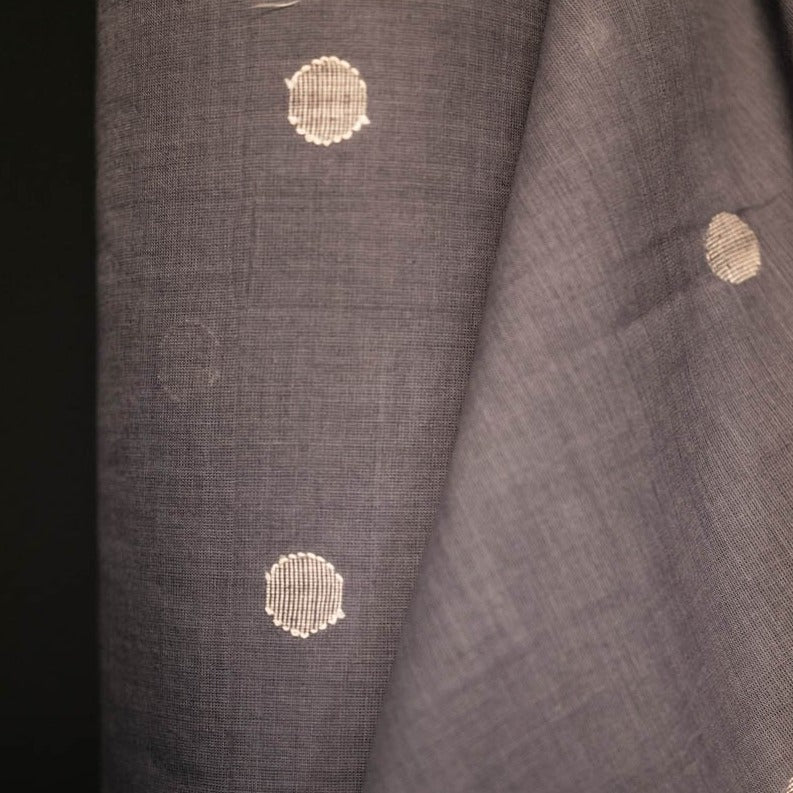 Jamdani Grey Spot Woven Cotton by Merchant and Mills.  A slate grey indian cotton with ecru woven spots. Jamdani is fine muslin cotton with small geometric motifs, it's a highly skilled weaving technique that has been practiced in India for centuries. This cloth comes alive once washed, it gets much softer and has a beautiful slub and texture.  Stitch Piece Loop, Australia.