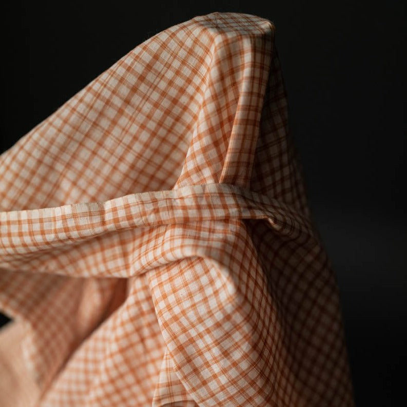 Marmalade Times Woven Cotton by Merchant and Mills.  A fine peach check on a warm white background . This cotton is very soft and lightweight so would work for tops, shirts, pyjamas and dresses with fullness or lining.  Stitch Piece Loop, Australia.
