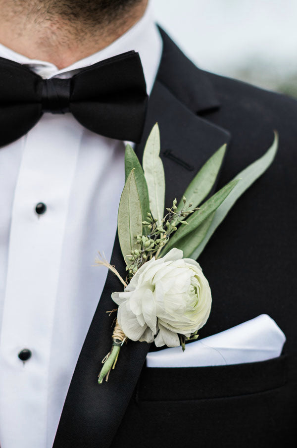 simple refreshing white rose and greenery Boutonniere for groom