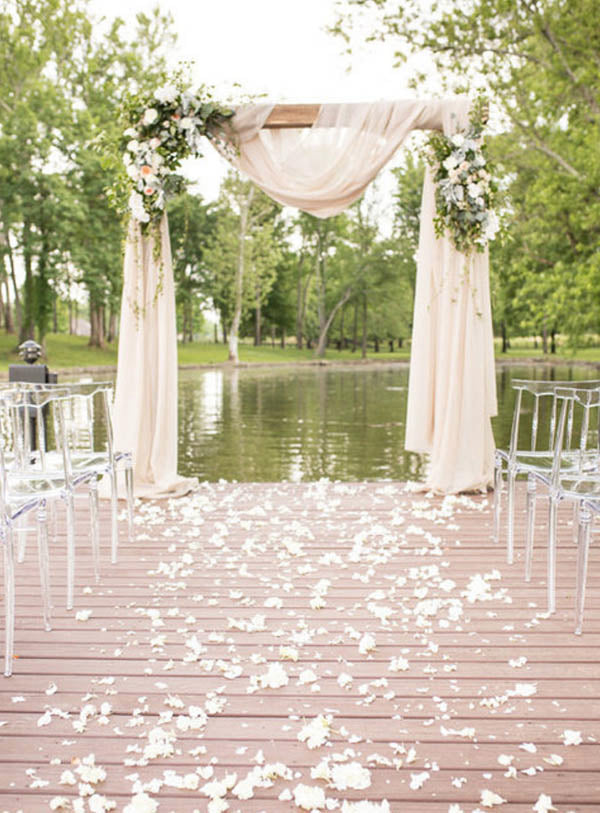 Lakeside outdoor wedding arch with pink drape and rustic flower decor