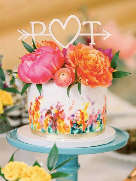 Create a striking contrast by topping your white wedding cake with a bouquet of vibrant flowers