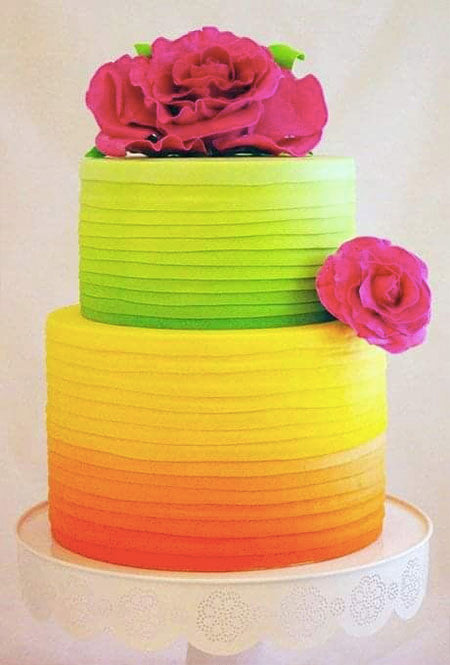 striking bold contrast magenta flower topper and wedding cake with a bouquet of vibrant flowers