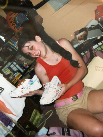 a teenager happily holding a pair of sneakers decorated with colorful doodles