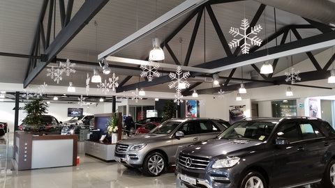 Christmas snow flake ornaments dangling from the roof of car showroom