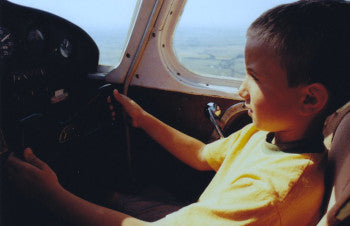Young boy flying piper aircraft