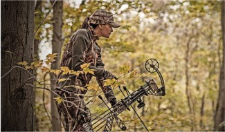 A woman in hunting clothes doing hunting