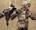 kid in a hunting jacket just captured a duck