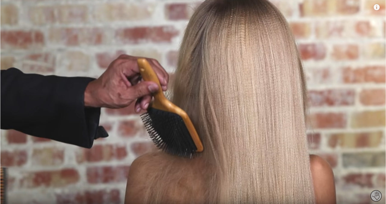 Hold the detangling brush vertically at an angle when removing tangles from hair
