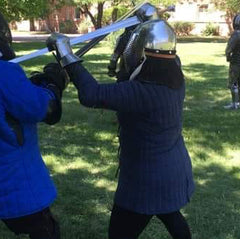 Short woman fencing outdoors against a taller partner. She is wearing a dark blue gambeson, black tights, steel gauntlets and a steel helmet, and using a half-swording technique in an upper guard.