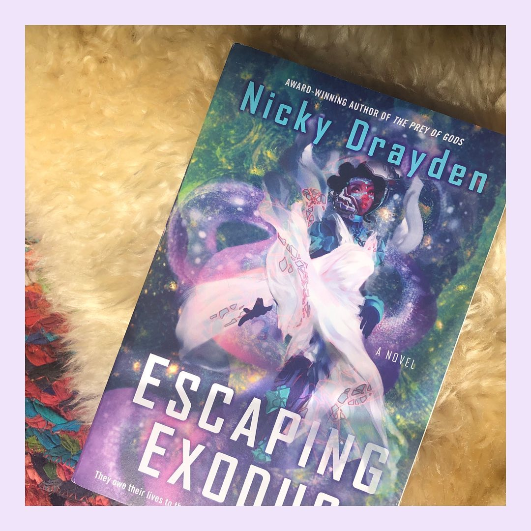 Escaping Exodus by Nicky Drayden. The book sits on top of a fluffy white mat and colorful mat.