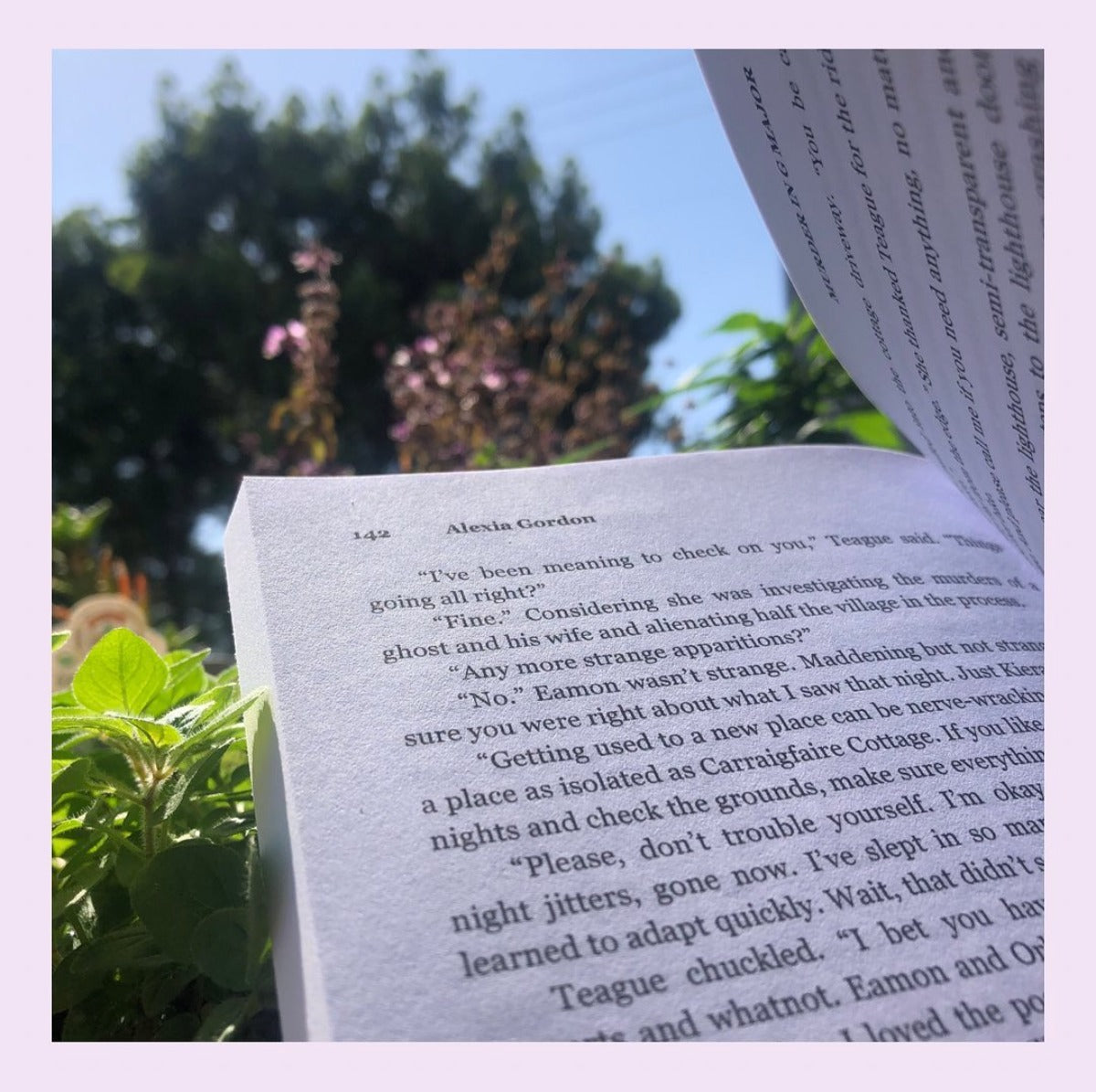 An open book sits on top of green plants. Murder in G Major by Alexia Gordon.