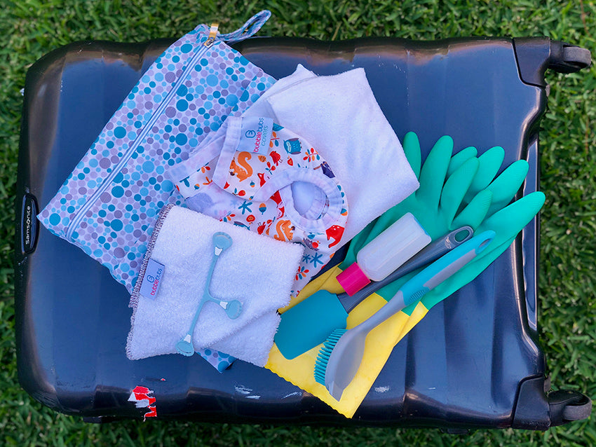 Suitcase, on grass with accessories for travelling with cloth nappies on top.