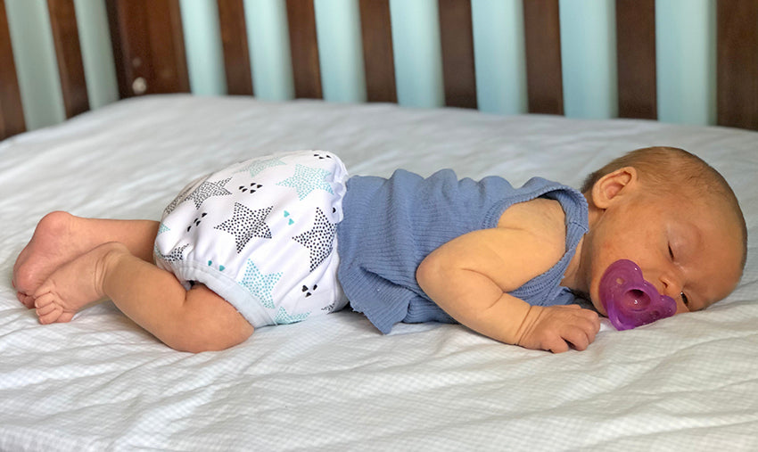 Newborn baby sleeping with bamboo prefold with star cover.