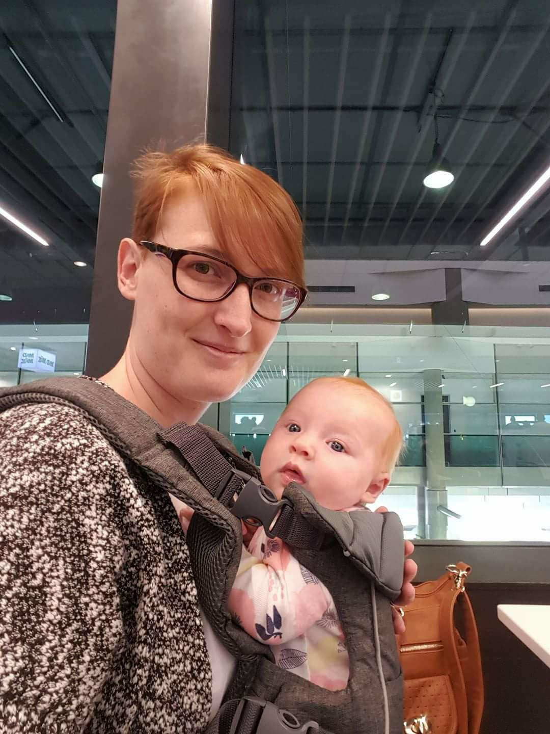 Red haired mother with baby in a carrier smiling at the camera.