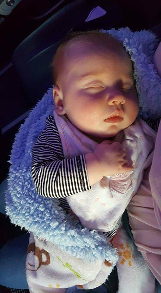 Sleeping baby in mother's arms on a plane.