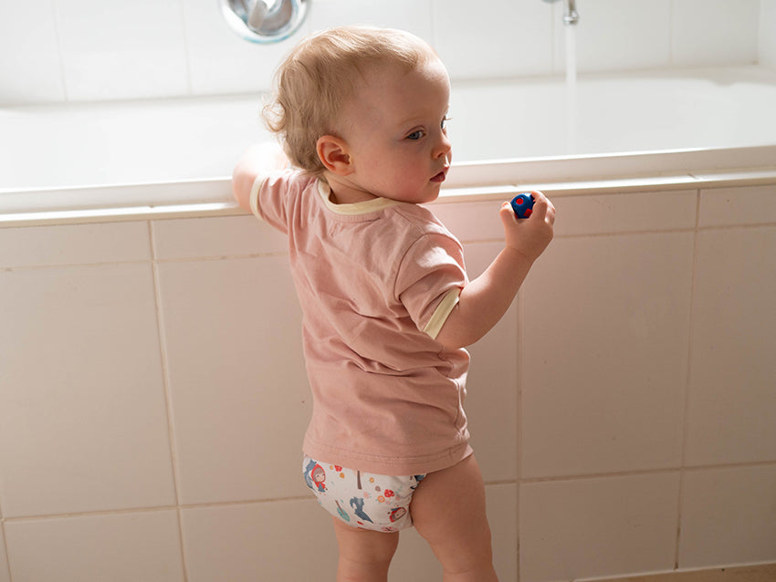 Toddler standing in front of a bath wearing an all in two cloth nappy