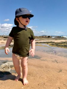 Toddler walking along the beach in Australia wearing a modern cloth all in two nappy.