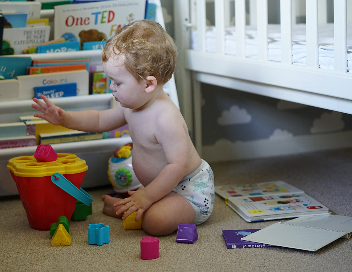baby playing with blocks wearing cloth nappy prefold