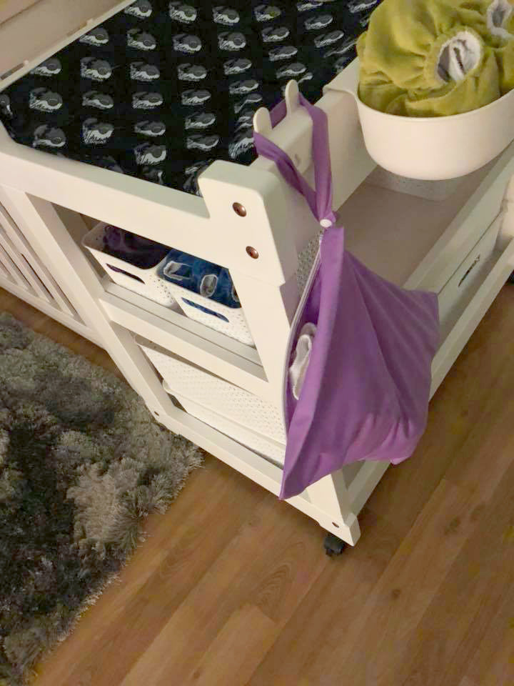 Purple wetbag hanging off a baby's change table.