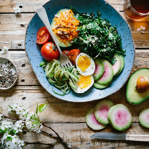 Salad in a bowl with eggs, greens, tomato, and other fruits and vegetables