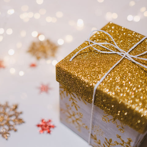 Present wrapped in a glittery gold box with glittery gold and red snowflakes around it