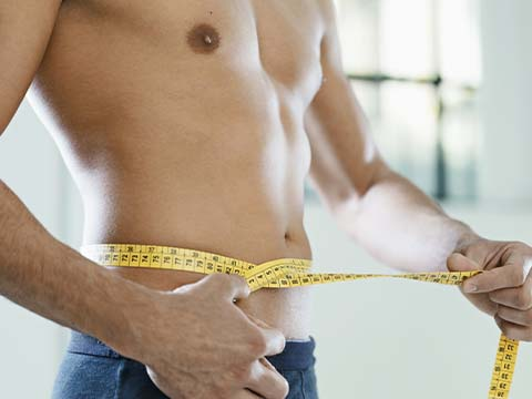 fit man holding measuring tape around his waist