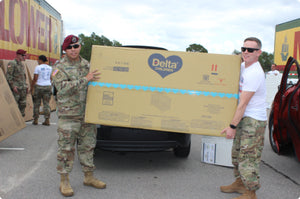 Soliders holding a Delta Children package
