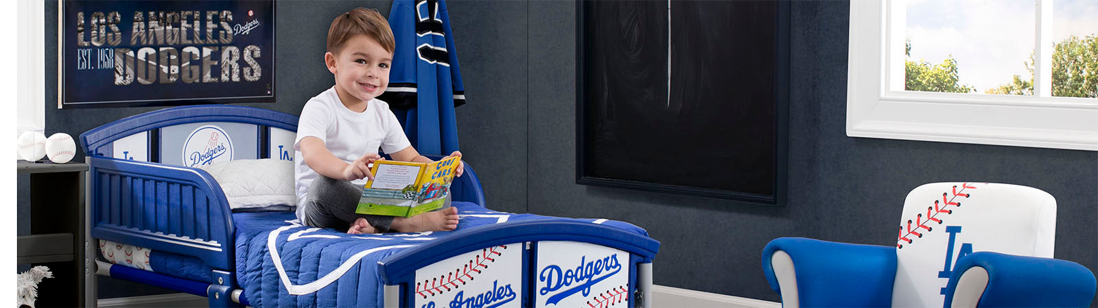 Little Boy sitting on his LA Dodgers Toddler Bed
