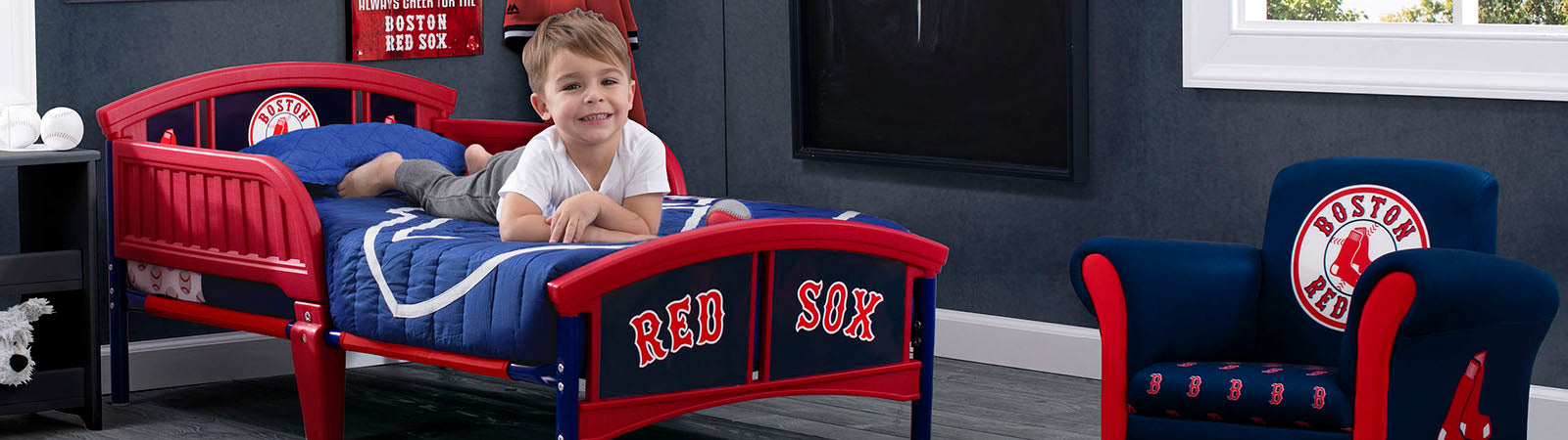 Little Boy lying down on his Boston Red Sox Toddler bed