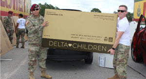 Soliders holding a Delta Children box