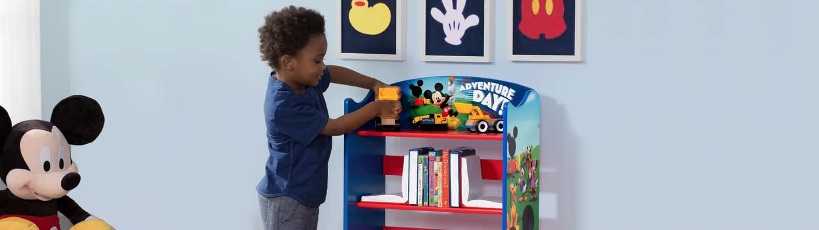 A young boy playing with toys on his bookshelf in his bedroom & Toy Boxes u0026 Book Storage | Delta Children