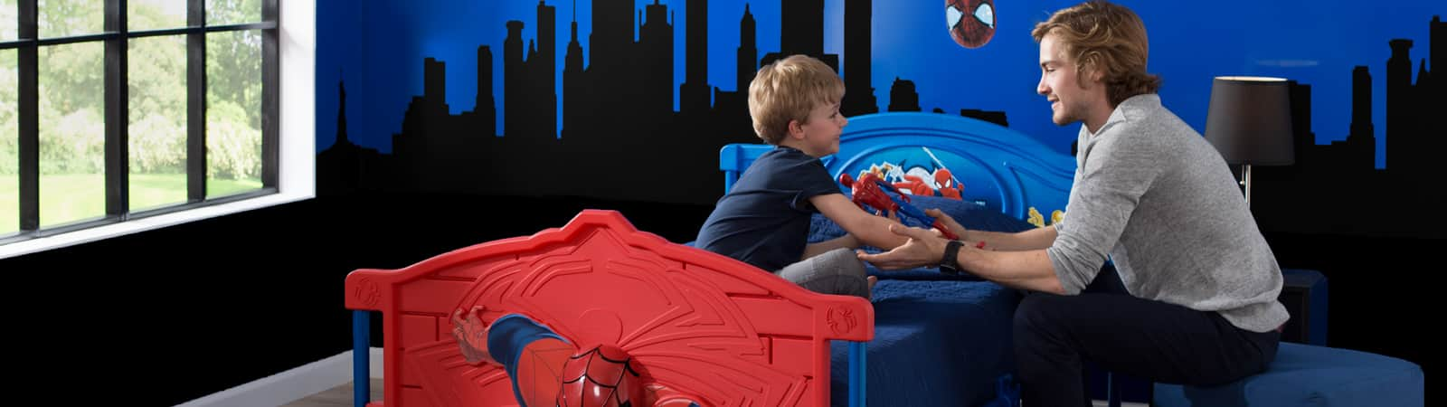 A father talking to son on his Spider-Man Twin bed before bedtime.