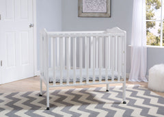 Delta Children Bianca (130) Portable Folding Crib with Mattress, room shot a1a