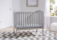 Delta Children Grey (180) Portable Folding Crib with Mattress, room shot b1b