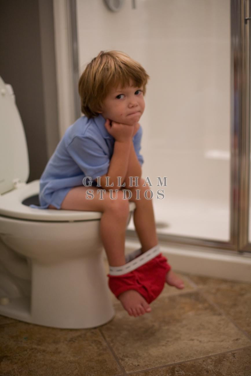 young boy and the toilets Little boy sitting on toilet with head in hands stock imagery by Gillham  Studios only at Gillham Studios