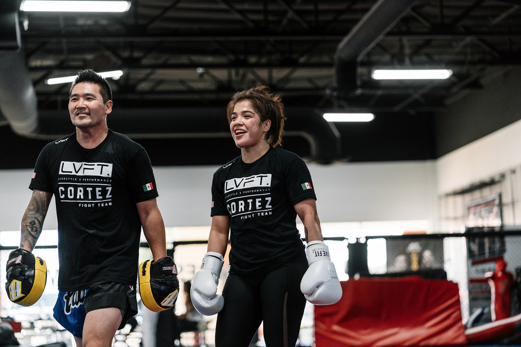 Striking coach Eddie Cha and fighter Tracy Cortez all smiles after a rigorous session.