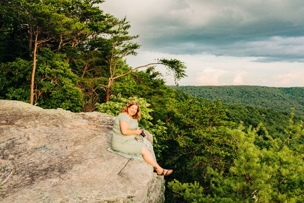Andrea Kruszka sitting on the edge of the cliff at Welch Point in Sparta, Tennessee