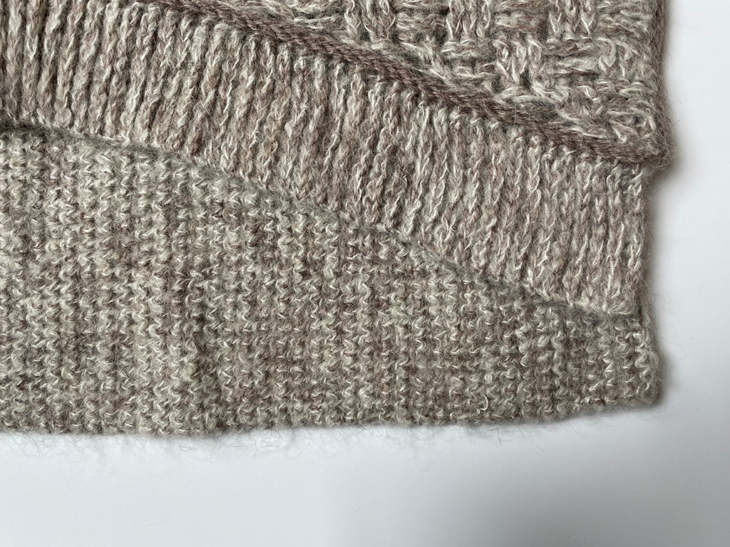 Close-up of front hem ribbing which is cropped shorter than the back