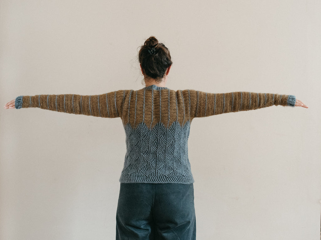 When viewed from the back and with arms raised, there is some excess material at the shoulder.