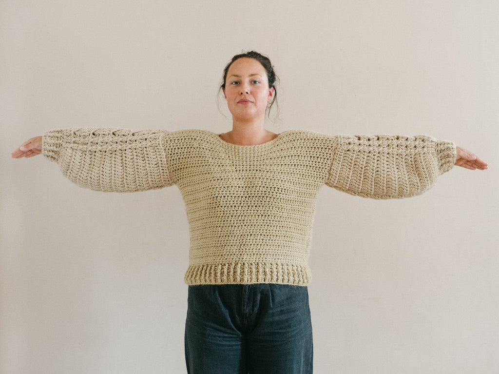 Model with arms raised showing wide sleeves drooping down from the arms