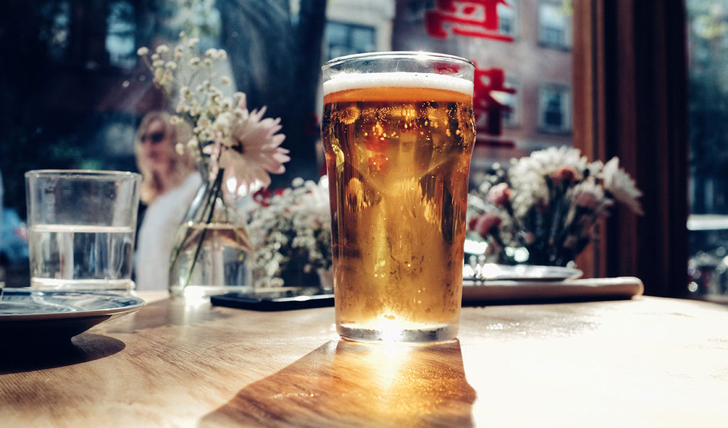 A pint of cider or beer on a table in a bar