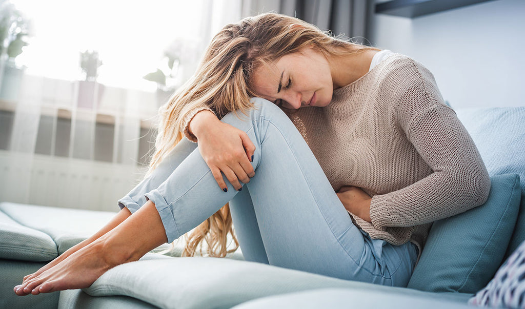 Woman with stomach ache on sofa