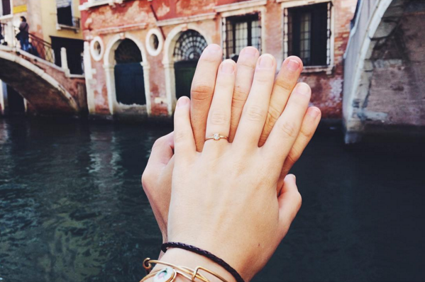 A newly engaged couple in Venice, Italy with an Alexis Russell ring.