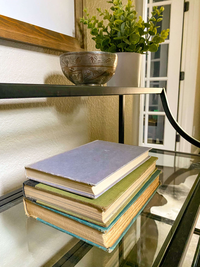 Intentionally Designed elements of an entryway console including a stack of books, organics and drop zone metal bowl.
